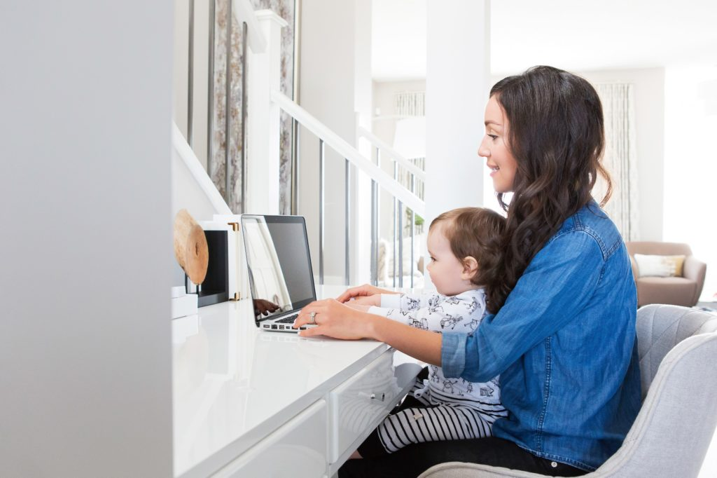 Woman with child working on laptop