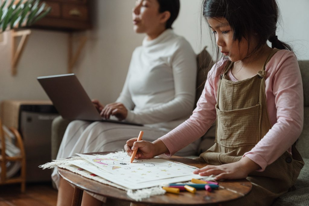 mom working on computer while kid draws