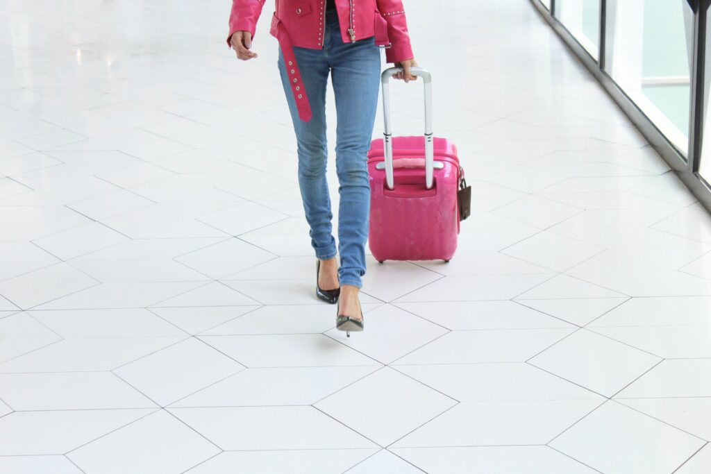 woman at airport with luggage wearing heels and pink jacket